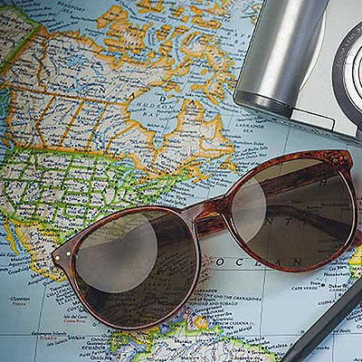 Sunglasses and camera on a map.